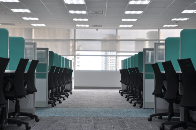 Photo of empty office space with desk chairs and cubicles