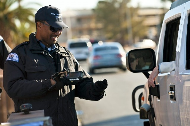 Paris Garrett, TW and Company security officer, scans identification cards using a biometric identification sensor at the Nellis Main Gate, March 20, 2012 at Nellis Air Force Base, Nev. Nellis is introducing a new security program, the Defense Biometric Identification System, to manage personnel, property and installation access. (U.S. Air Force photo by Senior Airman Brett Clashman)